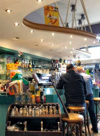 Inside a 1950s cafe in Le Havre, curvy bar in bright colours