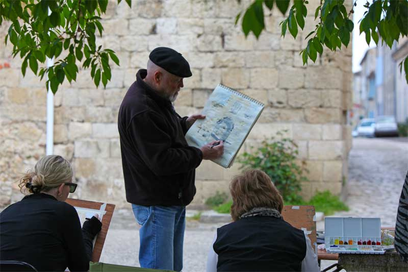 Artist shows a group how to draw at a workshop in open air, Gers