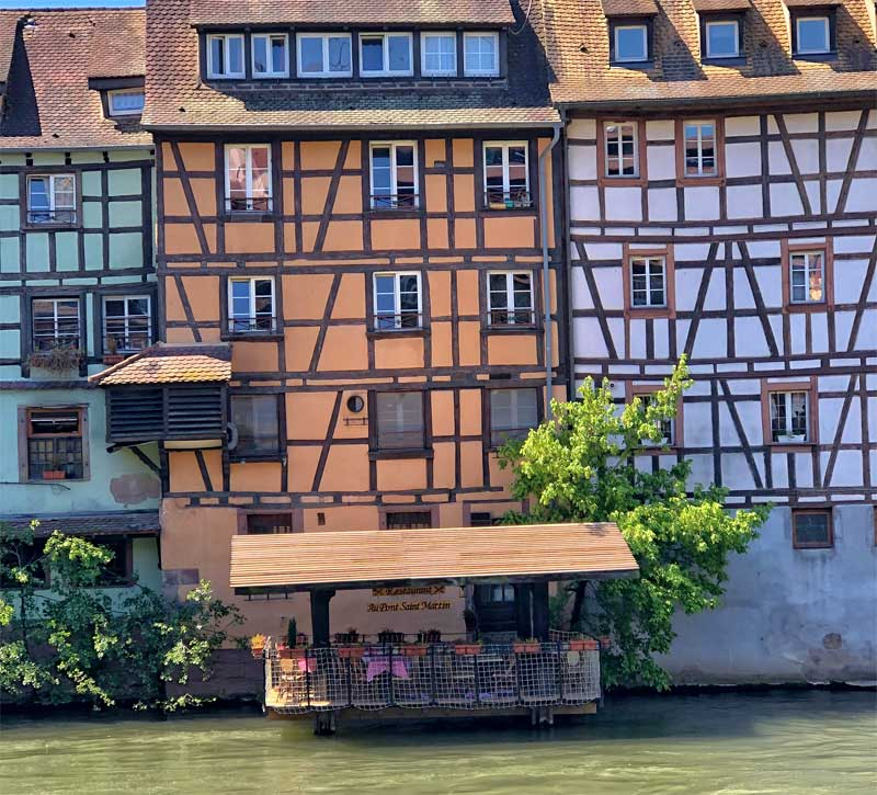 Colourful medieval houses and a wash house on the river converted to a restaurant terrace, Strasbourg