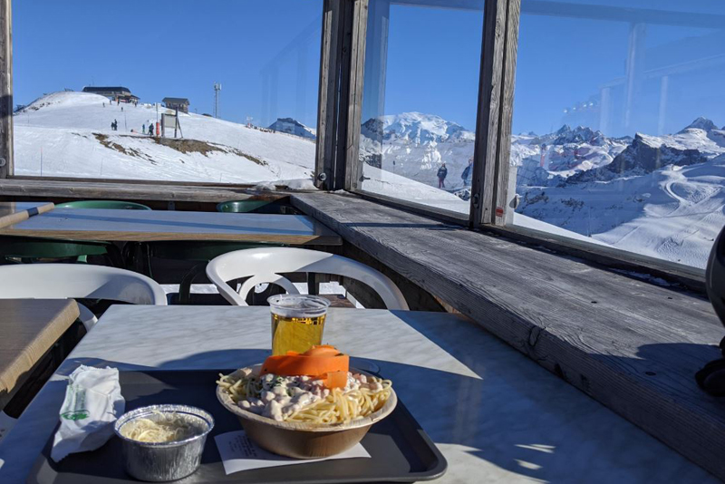Restaurant with a view, dish on a table overlooking the snow covered mountains