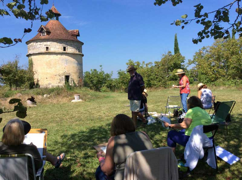 People taking a painting workshop in open air in the village of Fources, Gers, France