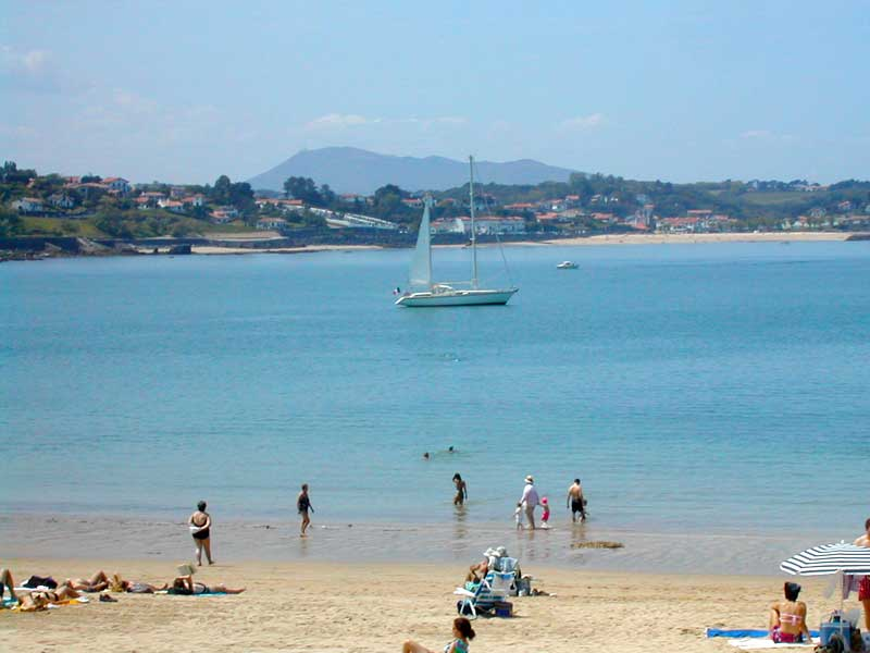 Golden sands and turquoise sea with a mountain backdrop in the Midi Pyrenees, France