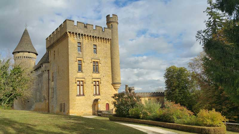 Chateau Puymartin in Dordogne, tall towers and turrets in mellow stone