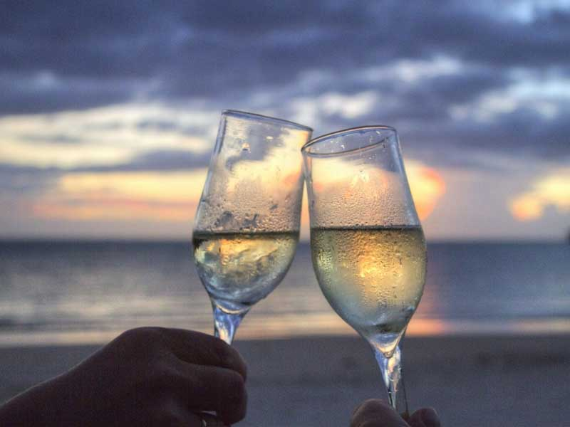 Two glasses of wine against a colourful sunset