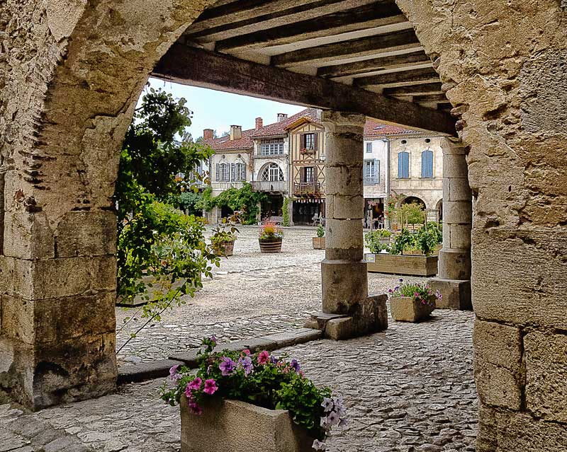 Medieval village with stone arches and a covered arcade and half-timbered houses, Gascony