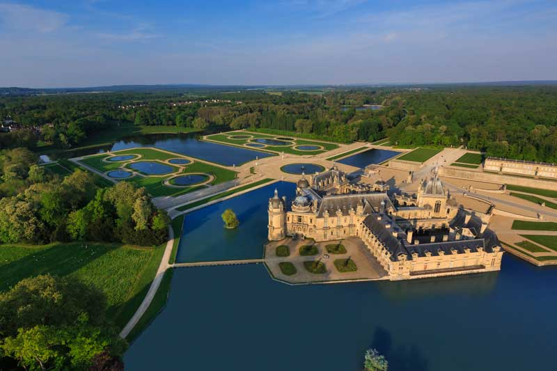 Aerial view of Chateau de Chantilly showing it surrounded by lakes and forests