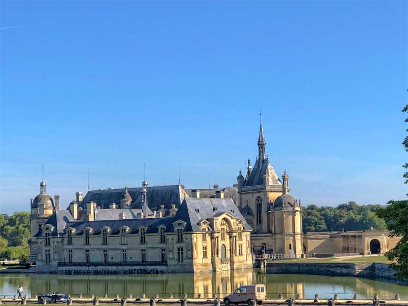 View of the Chateau de Chantilly, Picardy France - turrets and towers against a sunny sky