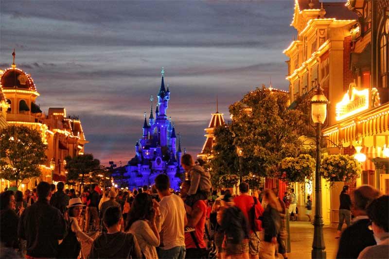 Illuminated Main Street Disneyland Paris at night, many people walking the street