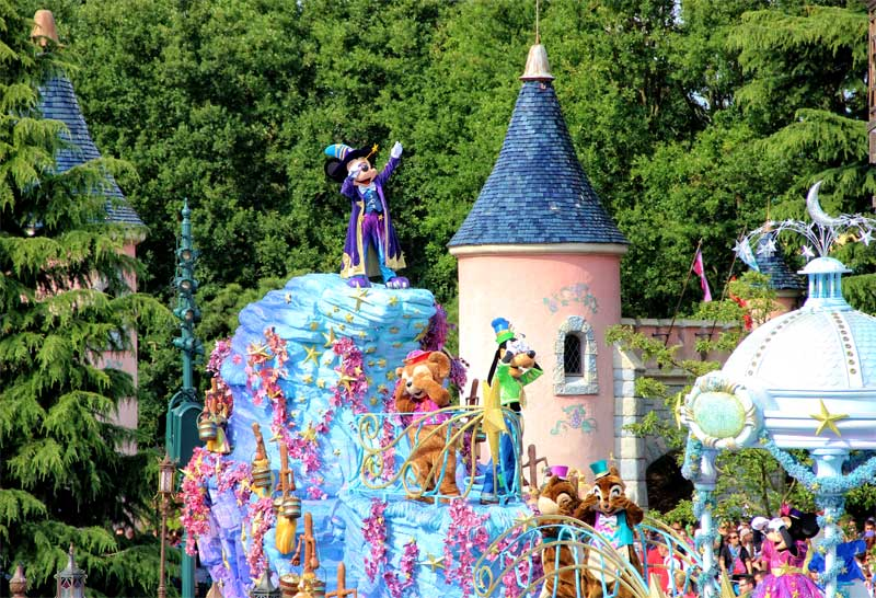 Micky Mouse atop a float at a parade in Disneyland Paris