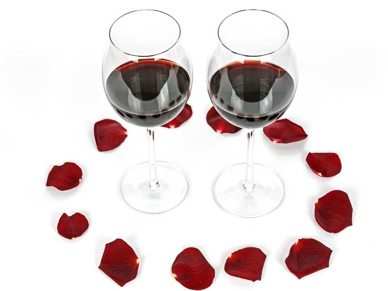 Glasses of red wine and rose petals