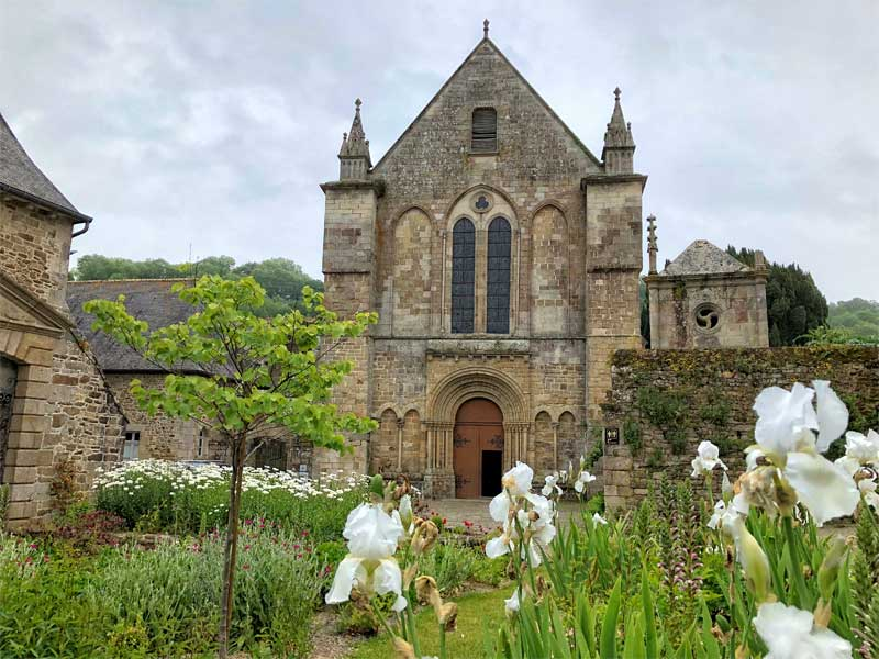 Abbey and gardens at Leon, bright flowers against ancient stonework