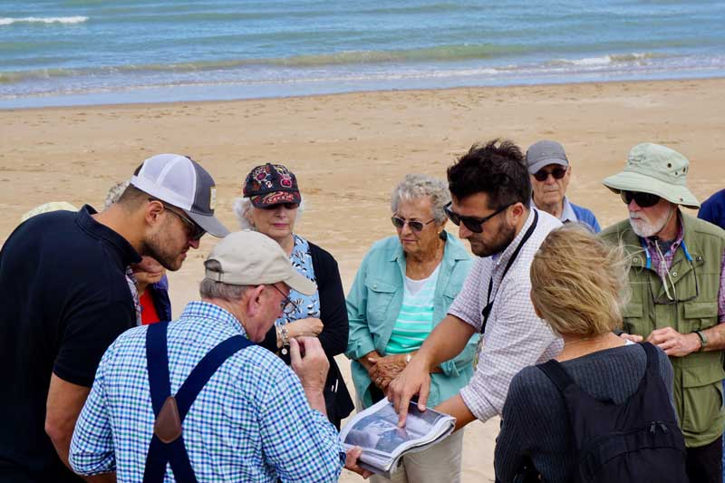 People with a guide looking at wartime photos of Omaha Beach, Normandy
