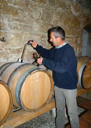 Man ladling wine from a barrel in a cellar in Provence