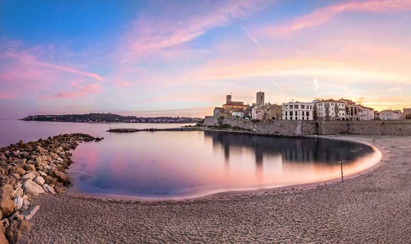 Bay of Antibes at sunset under a pink-tinged sky