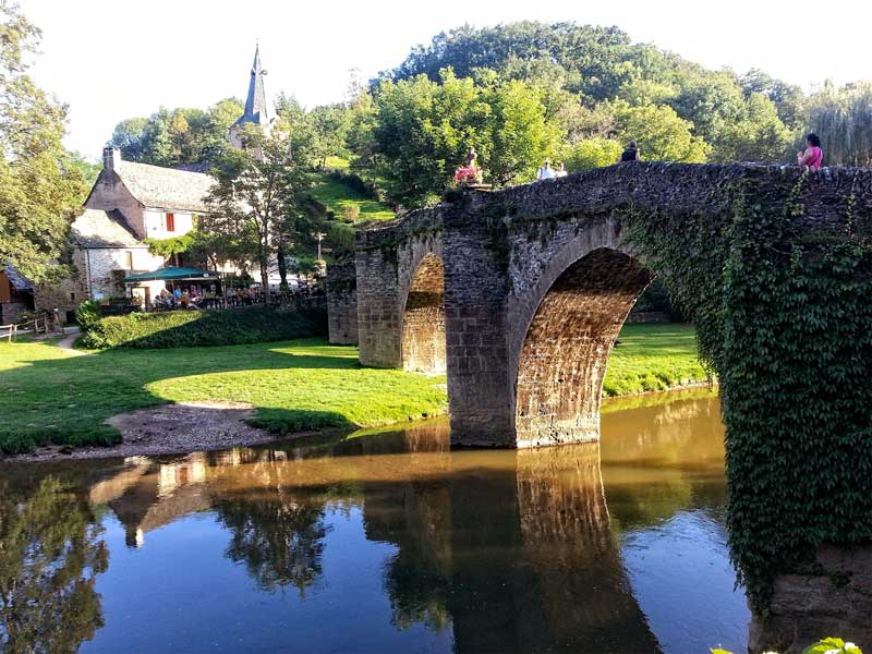 Ancient, arched stone bridge over a river leading to a town with old buildings and a church, Belcastel