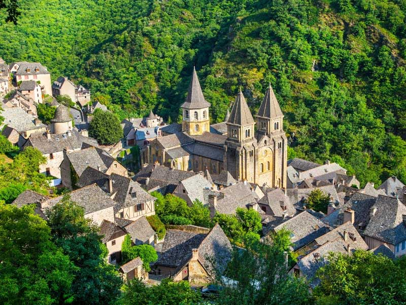 The church of Conques soars over the town, surrounded by forests and valleys