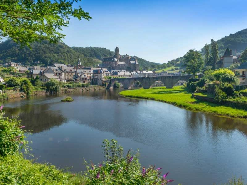 Village at the side of a river, dominated by an ancient castle, Estaing in Aveyron, sw France