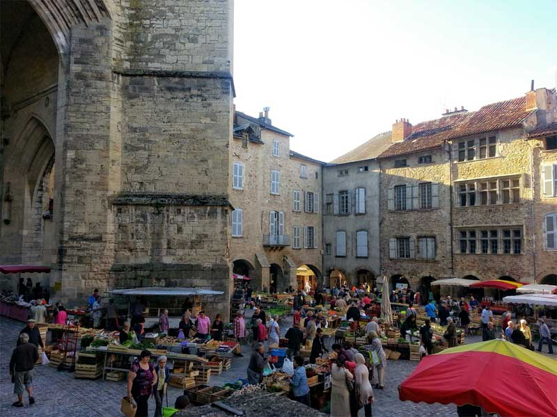 Market in a grand cobbled square before an imposing church in Villefranche-de-Rouergue, Aveyron