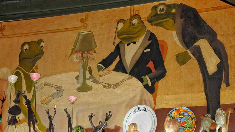Wall mural in a restaurant, frogs eating a table and a frog waiter