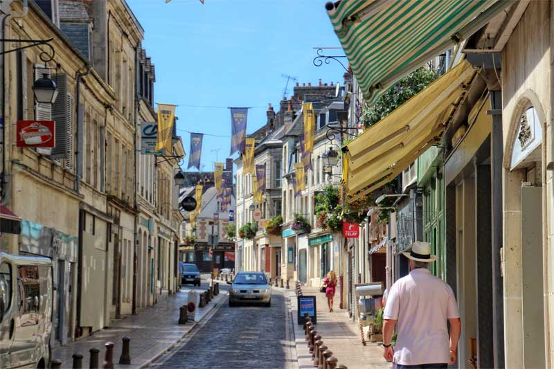 Cobbled street in Laon, Picardy, bunting hangs and shop awnings create colour