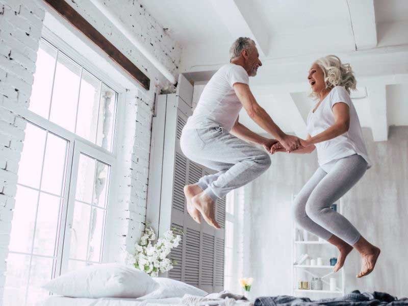 Elderly man and woman jumping up and down on a bed