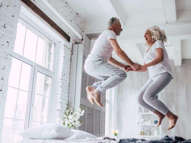 Personnes âgées homme et femme sautant de haut en bas sur un lit
