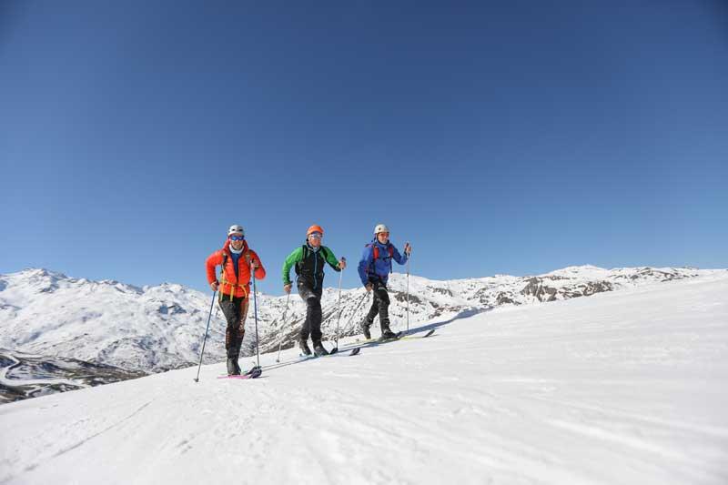 Trois skieurs sur une montagne enneigée