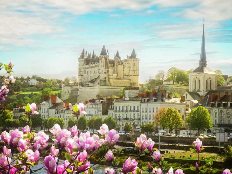 Spring flowers and fgreen hills surround the turreted Chateau of Saumur, Loire Valley