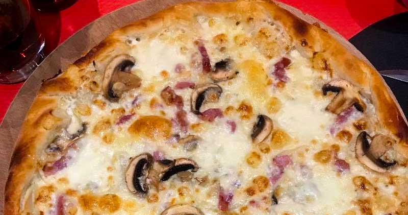 Tarte flambee a classic French pizza style dish topped with cheese and mushrooms