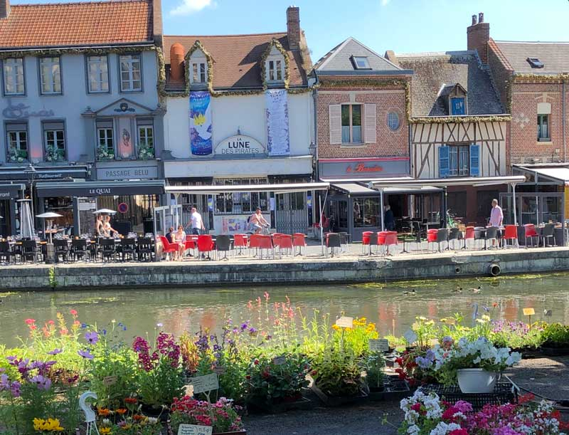 Market set out along the quay of Saint-Leu, half timbered houses and colourful cafes