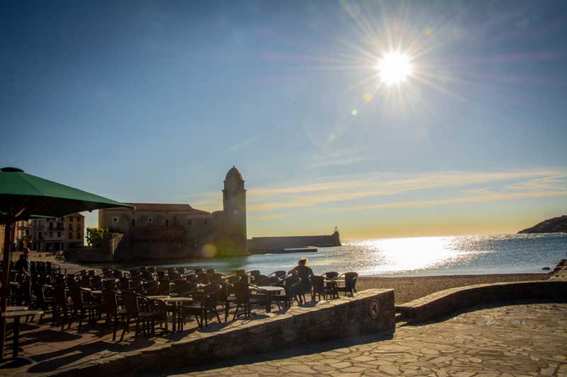 Sun rising over the beach at Collioure, southern France, a woman sits on an empty terrace, watching