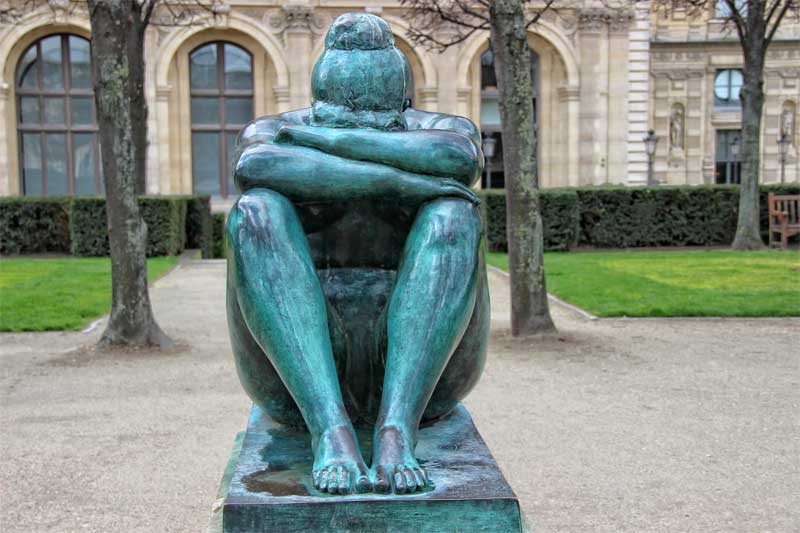 Bronze statue of a sitting woman, arms folded, head bent, Tuileries Garden, Paris