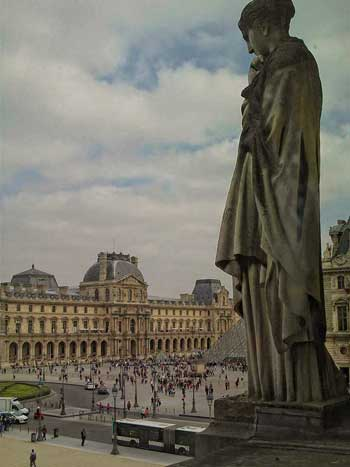 Statue of a woman looking at the Louvre Museum in Paris