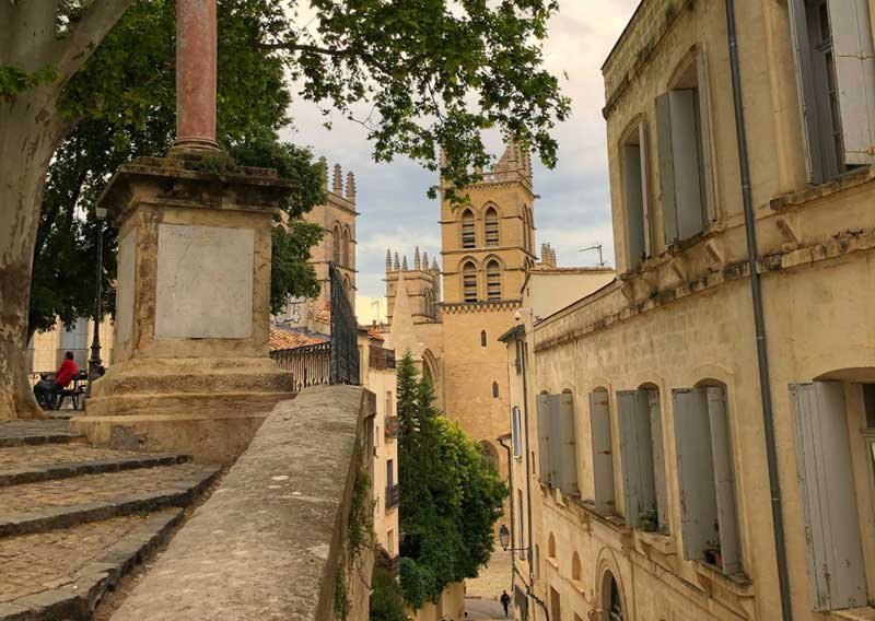 View of St Pierre Cathedral Montpellier, mellow, yellow stone buildings with grey shutters