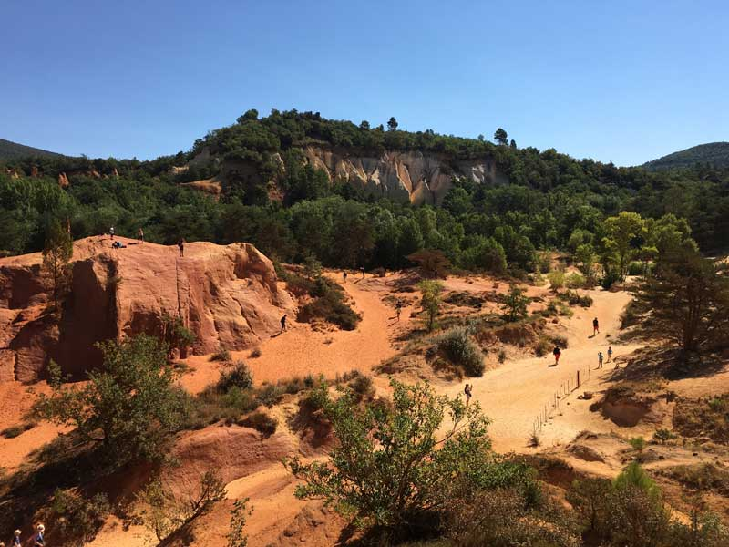 Roussillon ochre cliffs and quarries in Provence, russet coloured landscape with trees