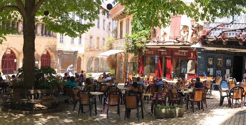Tables and chairs outside a restaurant, shaded by leafy trees in Saint-Antonin-Noble-Val, France