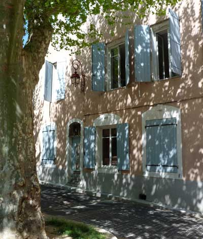 Stone house with pale blue shutters and dappled light through the leaves of a plane tree, Provence