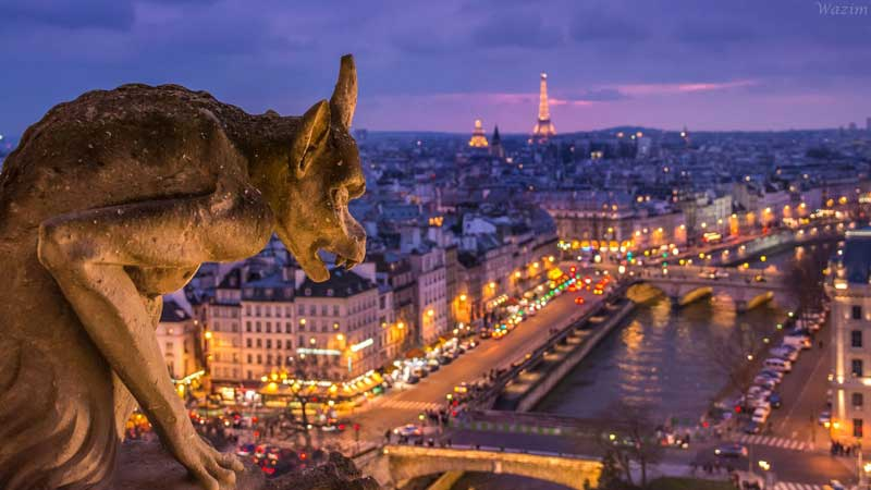 Pointy eared stone gargoyle on the roof of Notre-Dame Cathedral looking over Paris