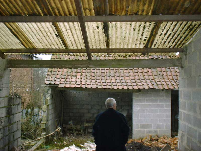 Man stands in a tumble down room with walls missing and holes in the roof