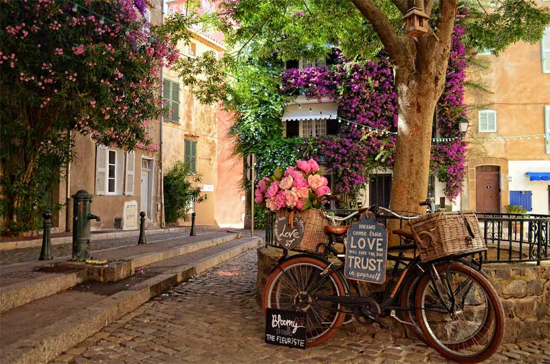 Push bike with a basket full of flowers in a shady square in St Tropez, France