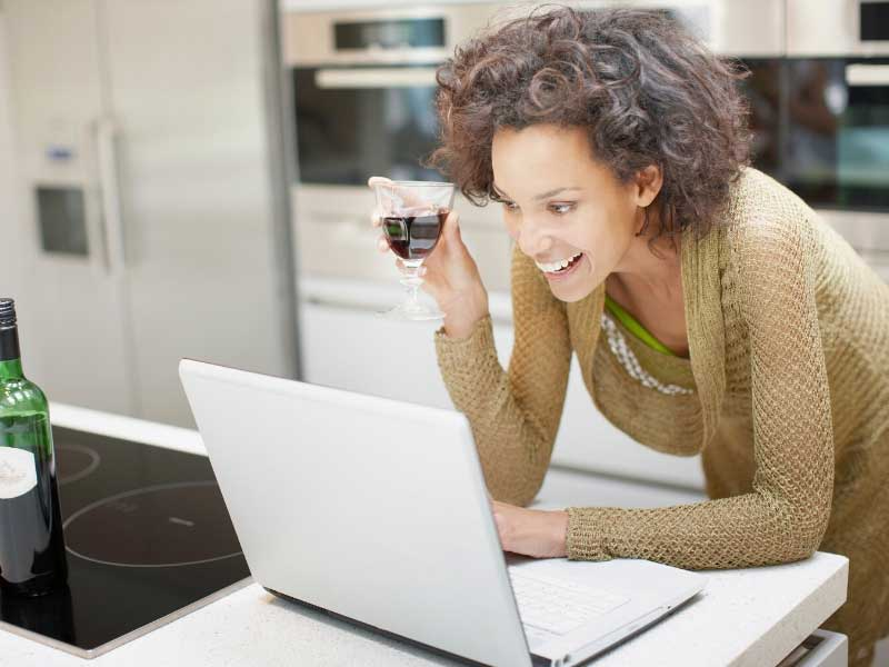 Woman drinking a glass of wine whilst chatting on a laptop with friends