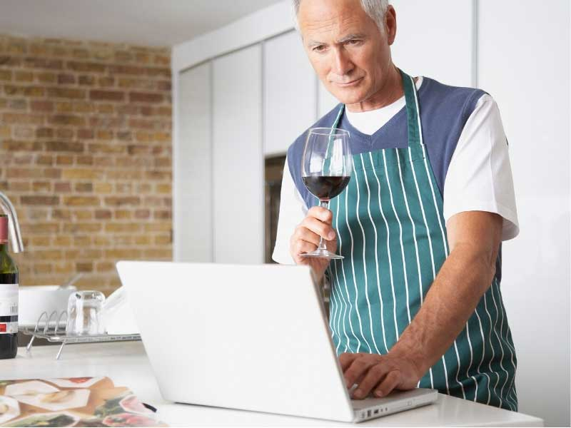 Man making joining an online cookery meeting with friends and drinking a glass of wine