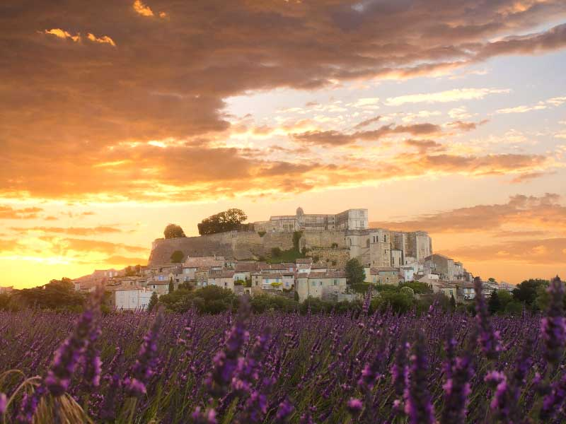 Hill top castle on a dusky night surrounded by lavender fields