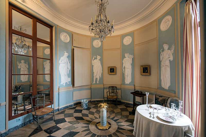 Room in a mansion in Le Havre with chandelier, mirrors, tiled floor, elaborately decorated in blue and white