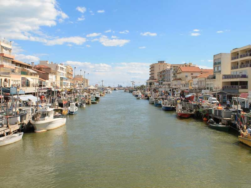 A river leads to the sea in Palavas-les-Flots, southern France, cafes line the quaysides, boats bob in the water