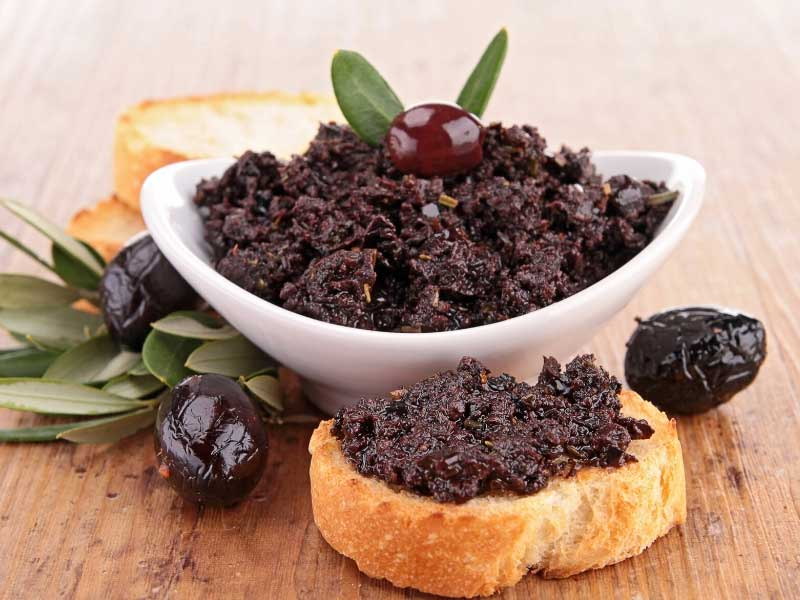 Bowl of black olive tapenade and a slice of bread spread with tapenade