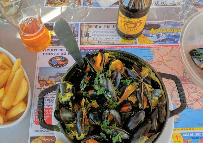 A steaming bowl of mussels with chips and cider in Brittany