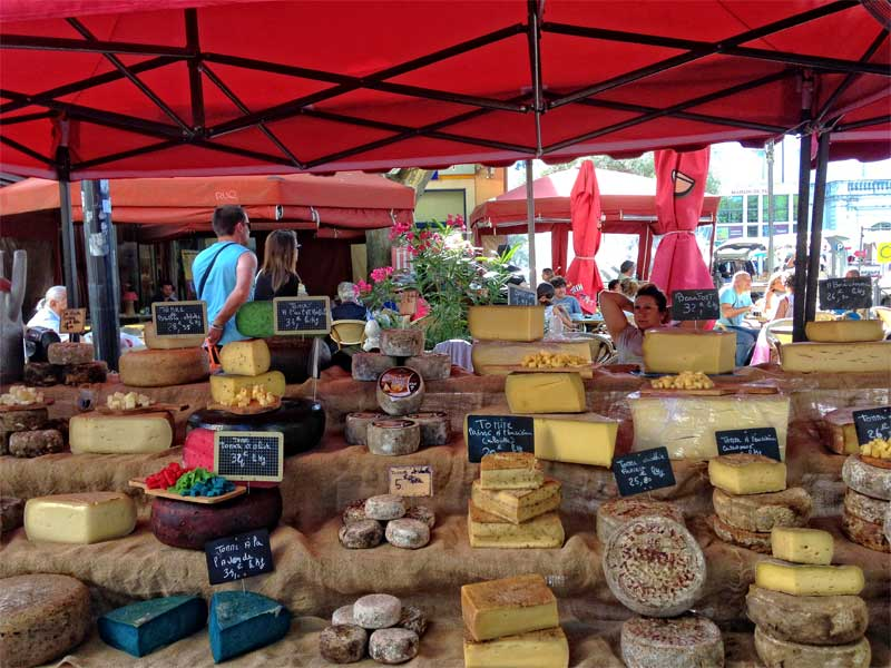 Cheese stall filled with French cheeses under a red awning at Carpentras market
