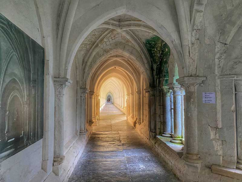 Very long cloisters of the Charterhouse of Neuville, sunlight casts a golden glow on the ancient paving