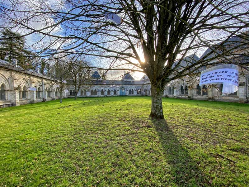An immense, grassy courtyard, surrounded by cloisters, Charterhouse of Neuville